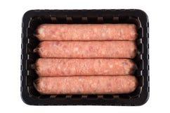 Quatro salsichas cruas na caixa plástica preta isolada no branco fotografia de stock