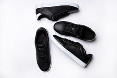 Quatro sapatilhas de couro pretas com sola branca em um fundo branco imagem de stock royalty free