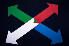 Quatro setas coloridas na obscuridade - fundo azul Conceito do negócio fotos de stock royalty free