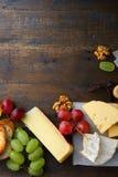 Quatro tipos de queijo com uvas e nozes na tabela de madeira velha Fotos de Stock Royalty Free