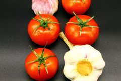 Quatro tomates maduros suculentos vermelhos e duas cabeças do alho em um fundo preto imagens de stock