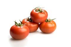 Quatro tomates vermelhos realísticos empilhados acima do isolado no fundo branco Fotos de Stock Royalty Free