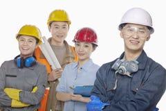 Quatro trabalhadores da construção de sorriso contra o fundo branco, foco no primeiro plano, olhando a câmera imagem de stock