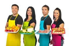 Quatro trabalhadores do mercado com seus produtos Foto de Stock