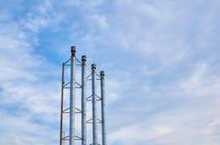 Quatro tubulações da sala de caldeira contra o céu azul com nuvens Fotos de Stock Royalty Free