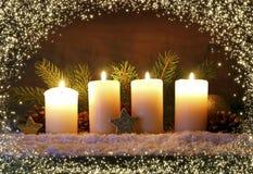 Quatro velas ardentes do advento e luzes luminosas Imagem de Stock Royalty Free