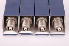 Quatro velas de ignição novas no empacotamento de papel Fotos de Stock Royalty Free