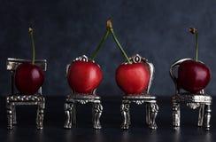 Quatro vermelho - cerejas deliciosas colocadas em cadeiras de prata minúsculas na obscuridade Imagem de Stock Royalty Free