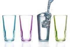 Quatro vidros bebendo coloridos, um com água Fotografia de Stock Royalty Free