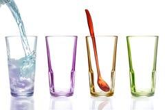 Quatro vidros bebendo coloridos, um com água Imagem de Stock Royalty Free