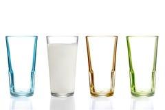 Quatro vidros bebendo coloridos, um com leite Fotos de Stock Royalty Free