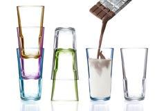 Quatro vidros bebendo coloridos, um que está sendo enchido com o leite de chocolate Imagem de Stock