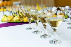 Quatro vidros do champanhe na tabela de banquete Fotos de Stock