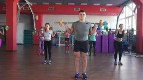Quats con los pesos en el entrenamiento Grupo de mujeres jovenes y de hombre en la clase de aeróbicos que hace ejercicios Muchach almacen de video