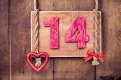 Quattordici schede dell'annata del biglietto di S. Valentino, cuore che appende sul fondo di legno della parete Immagini Stock Libere da Diritti