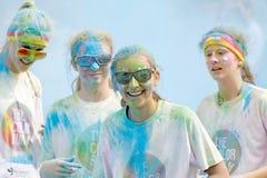 Quattro adolescente e vetri sorridenti coperti di colore spolverano Fotografia Stock