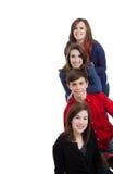 Quattro adolescenti che sorridono su una priorità bassa bianca Fotografie Stock Libere da Diritti