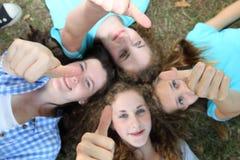 Quattro adolescenti felici che danno i pollici aumenta Immagine Stock