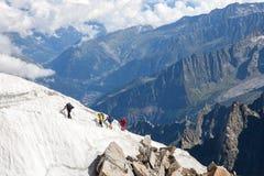 Quattro alpinisti salgono a sulla toppa della neve Fotografie Stock Libere da Diritti