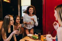Quattro amiche allegre divertendosi cibo di chiacchierata e di risata e bere nel fast food Immagini Stock