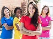 Quattro amiche con le camice variopinte nella città Immagini Stock Libere da Diritti