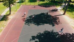 Quattro amici adatti che giocano pallacanestro sulla corte nell'aria aperta stock footage