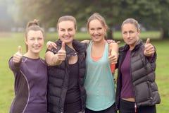 Quattro amici atletici delle donne che danno i pollici su Fotografie Stock Libere da Diritti