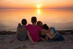 Quattro amici che abbracciano sulla spiaggia e che ammirano il tramonto Immagini Stock