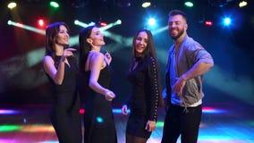 Quattro amici che ballano nel night-club nello scuro video d archivio