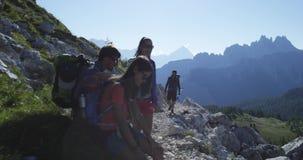 Quattro amici che camminano lungo il percorso della traccia di escursione e si rilassano Gruppo di viaggio di avventura di estate video d archivio