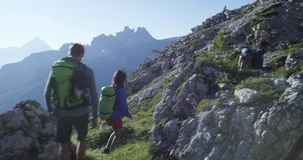 Quattro amici che camminano lungo il percorso della traccia di escursione Gruppo di viaggio di avventura di estate della gente de stock footage