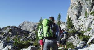 Quattro amici che camminano lungo il percorso della traccia di escursione Gruppo di viaggio di avventura di estate della gente de archivi video