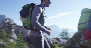 Quattro amici che camminano lungo il percorso della traccia di escursione Gruppo di viaggio di avventura di estate della gente de video d archivio
