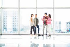 Quattro amici che parlano nel corridoio luminoso con le finestre panoramiche Immagine Stock