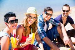 Quattro amici che si siedono sulla spiaggia del lago con i cocktail Immagini Stock