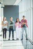 Quattro amici che stanno con le mani attraversate e che sorridono all'interno Studenti di Fours in università Immagine Stock Libera da Diritti
