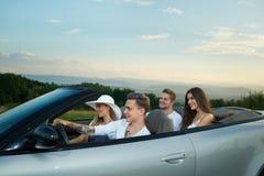 Quattro amici che vanno per l'azionamento, sedentesi in cabriolet d'argento fotografia stock libera da diritti