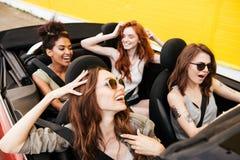 Quattro amici emozionali delle giovani donne che si siedono in automobile Immagini Stock Libere da Diritti