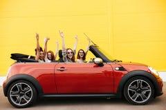 Quattro amici emozionali felici delle giovani donne che si siedono in automobile Fotografia Stock