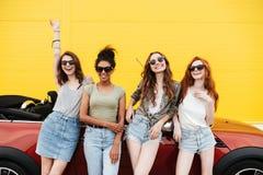 Quattro amici emozionali felici delle giovani donne che stanno automobile vicina Fotografie Stock