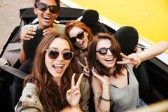 Quattro amici emozionali sorridenti delle giovani donne che si siedono in automobile Fotografia Stock Libera da Diritti