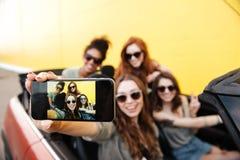 Quattro amici emozionali sorridenti delle giovani donne che si siedono in automobile Immagine Stock Libera da Diritti
