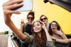 Quattro amici emozionali sorridenti delle giovani donne che si siedono in automobile Immagine Stock