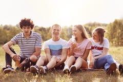 Quattro amici positivi hanno insieme gioia, hanno espressioni felici, si siedono su erba verde all'aperto, godono dell'ozio duran Fotografie Stock