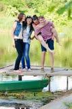 Quattro amici sorridenti felici si divertono sul pilastro sul fondo dell'estate all'aperto Fotografie Stock