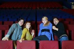 Quattro amici spaventati vedono il film nel teatro del cinema Immagine Stock