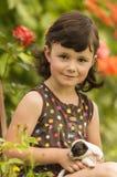 Quattro anni della ragazza che gioca con il cucciolo nel giardino Fotografia Stock