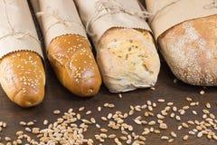 Quattro baguette e grano sulla tavola Immagine Stock