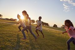 Quattro bambini che corrono a piedi nudi in salita in un parco immagine stock