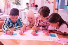 Quattro bambini che scrivono insieme su un quotidiano di grande formato immagine stock libera da diritti